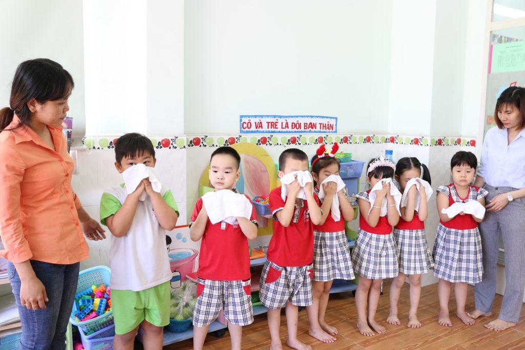 các bé dùng khăn lau mặt tại trường